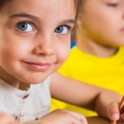 Junges Mädchen schreibt mit einem Bleistift