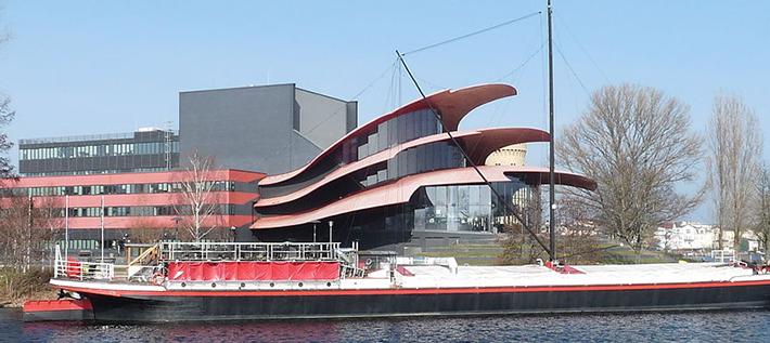Das Theaterschiff Potsdam vor dem Hans Otto Theater (Foto: wikipedia.de Biberbaer, Lizenz: CC BY-SA 3.0 https://creativecommons.org/licenses/by-sa/3.0)