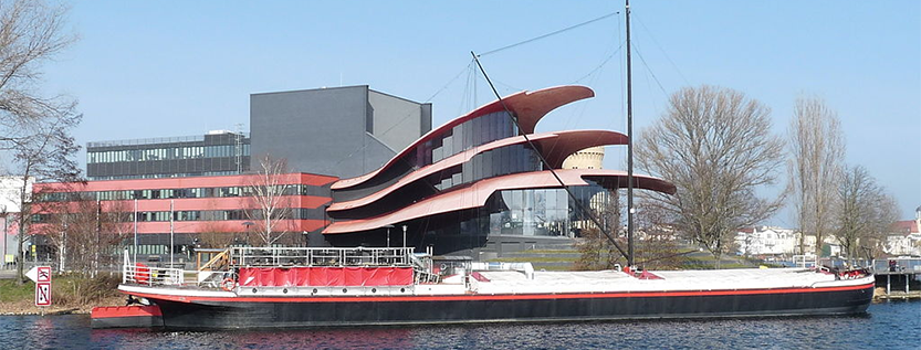 Das Theaterschiff Potsdam vor dem Hans Otto Theater (Foto: wikipedia.de Biberbaer, Lizenz: CC BY-SA 3.0 https://creativecommons.org/licenses/by-sa/3.0)